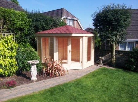 corner summerhouse with double doors and red hexagon felt shingled roof